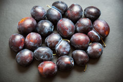 Plums on black background Stock Photos