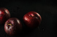 Plums on Black. Low key shot of Plums on a black, smooth and wet surface Royalty Free Stock Image