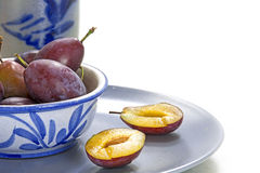 Plums in blue crockery, one of them is cut, white background Stock Photo