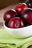 Plums in a bowl. Fresh plums in a bowl on napkin closeup Stock Image