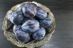 Plums in a bowl. On a dark wooden table Royalty Free Stock Photography