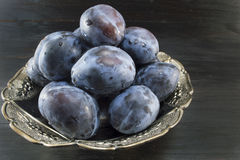 Plums in a bowl. On a dark wooden table Stock Photos