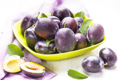 Plums in a bowl. Fleshy plums in a bowl on the table Stock Photos