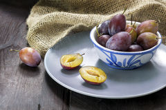 Plums in a bowl and on a plate on dark wood Royalty Free Stock Photography