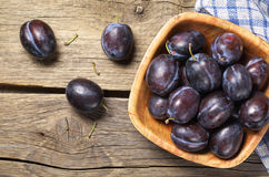 Plums in bowl. Ripe plums in bowl on rustic wooden background, top view Royalty Free Stock Photos