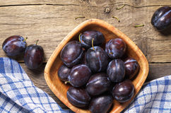 Plums in bowl. Ripe plums in bowl on rustic wooden table with napkin, top view Royalty Free Stock Photos