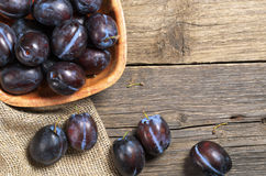 Plums in bowl. Ripe plums in bowl on rustic wooden table, top view Royalty Free Stock Photo