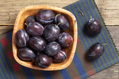 Plums in bowl. Ripe plums in bowl on rustic wooden table, top view Royalty Free Stock Images