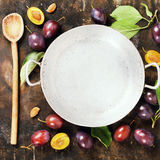 Plums in a bowl on a rural background Royalty Free Stock Image