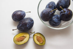 Plums in bowl on white Royalty Free Stock Images