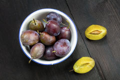 Plums in a bowl, whole and halved on dark brown wood Stock Photography