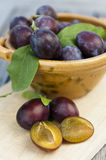 Plums with bowl on wood Stock Photography