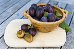 Plums with bowl on wood Stock Photos
