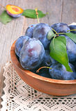 Plums in bowl. On wooden table Royalty Free Stock Photo
