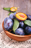 Plums in bowl. On wooden table Royalty Free Stock Photography