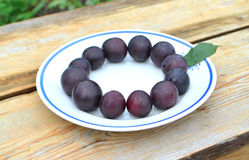 Plums in a bowl. On the wooden table Royalty Free Stock Photo