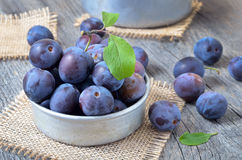 Plums in bowl. On the wooden table Stock Images