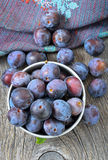 Plums in bowl on the wooden table Stock Image