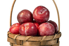 Plums in brown basket Royalty Free Stock Image