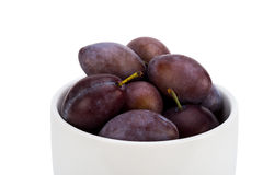 Plums in ceramic bowl. Isolated on white background Stock Image