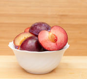 Plums In Ceramic Bowl On Table Royalty Free Stock Image