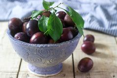 Plums in a clay bowl on a wooden table. Rustic style, selective focus. Stock Photo