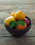 Plums in clay pot Stock Photos