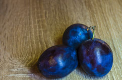 Plums. Closeup foto of plums on wood background Stock Images