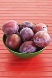 Plums, damsons in green plastic bowl on red wood Royalty Free Stock Photos