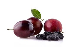 Plums with dried prunes on white background. Fresh plums with leaf and prunes royalty free stock image