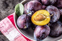 Plums. Fresh juicy plums in a bowl on a wooden or concrete board Stock Photography