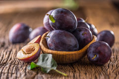 Plums. Fresh juicy plums in a bowl on a wooden or concrete board Stock Photo