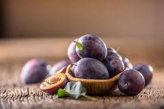 Plums. Fresh juicy plums in a bowl on a wooden or concrete board Royalty Free Stock Photos