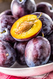 Plums. Fresh juicy plums in a bowl on a wooden or concrete board Stock Image