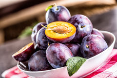 Plums. Fresh juicy plums in a bowl on a wooden or concrete board Royalty Free Stock Image