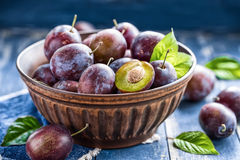Plums. Fresh plums with leaves on a plate royalty free stock photos