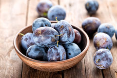 Plums. Fresh plums on wooden table close up Stock Images