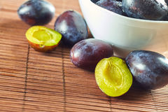 Plums in fruit bowl. Fresh plums in white bowl on wooden background. Copy space Stock Images