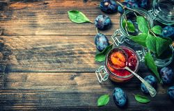 Plums fruit marmalade wooden background vintage. Plum fruit marmalade on rustic wooden background. Vintage style toned picture Royalty Free Stock Image