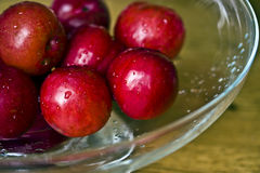 Plums in glass bowl. A glass bowl containing washed plums Stock Photo
