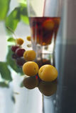 Plums. And the glass with compote on the table Stock Images