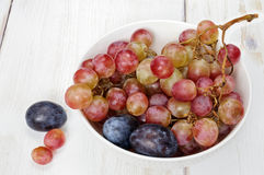 Plums and grapes in bowl on the white wooden table Royalty Free Stock Image