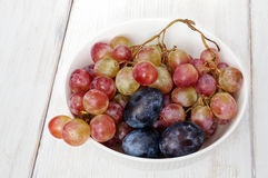 Plums and grapes in bowl on the white wooden table Stock Photos