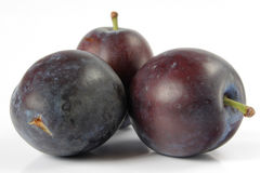 Plums isolated. Three plums isolated on white stock image