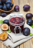 Plums jam. Plum jam in a glass jar with fresh plums on wooden background Stock Photography