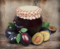 Plums jam with plums fruit. On wooden texture Stock Images