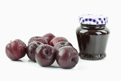 Plums beside jar of plum jam Stock Photos