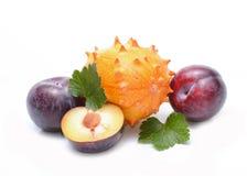 Plums and kiwano fruit Stock Photos