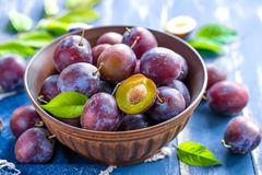 Plums. With leaves on a plate on a table Royalty Free Stock Image