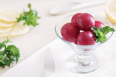 Plums lie in a glass cream bowl on the table, lemon cut into slices, fresh mint leaves, healthy foods, dietary berries and fruits, royalty free stock photo